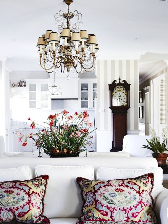 a modern space is made more eye-catchy with a vintage-inspired chandelier and a vintage clock