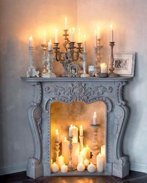 a whitewashed vintage fireplace with lots of candles inside and on the mantel