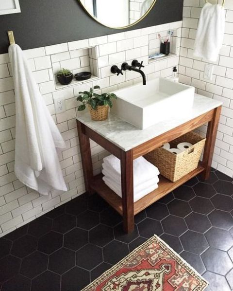 matte black hex tiles on the floor and matte white subway tiles with black grout for an elegant bathroom