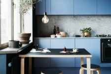 15 muted blue modern kitchen with a marble backsplash and sleek cabinets