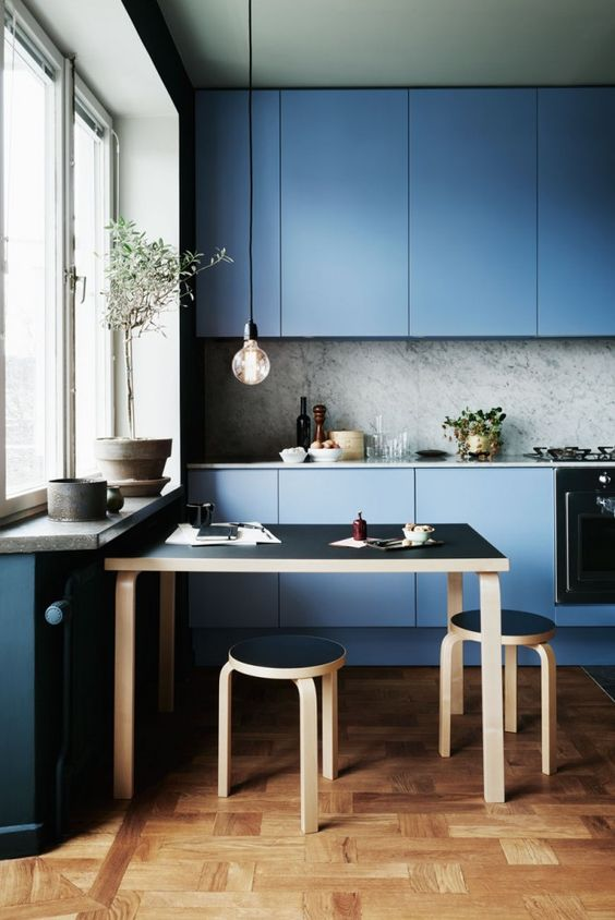 muted blue modern kitchen with a marble backsplash and sleek cabinets