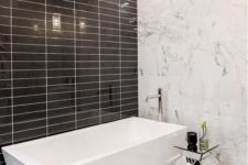 15 white marble, glossy black tiles and a geometric bathtub make this minimalist space really stand out