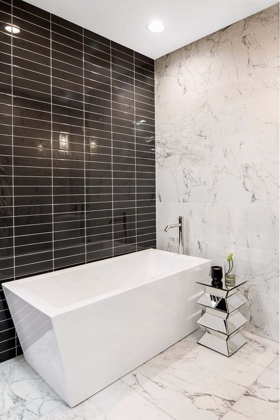 white marble, glossy black tiles and a geometric bathtub make this minimalist space really stand out