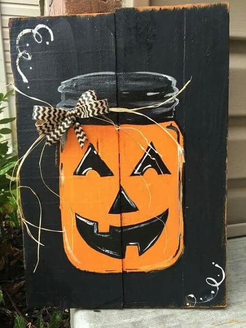a black pallet sign with a bold orange Jack-o-lantern, a ribbon bow