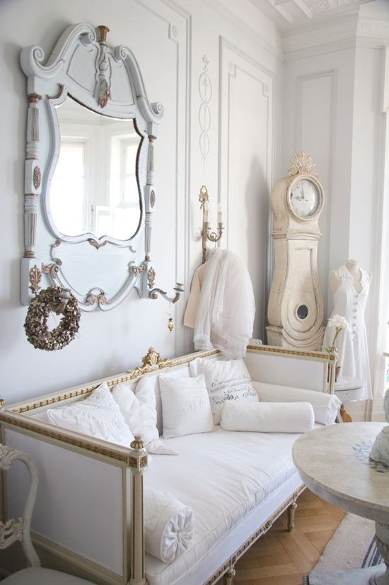 a luxurious interior in white, pastels and gold, with an antique mirror and clock