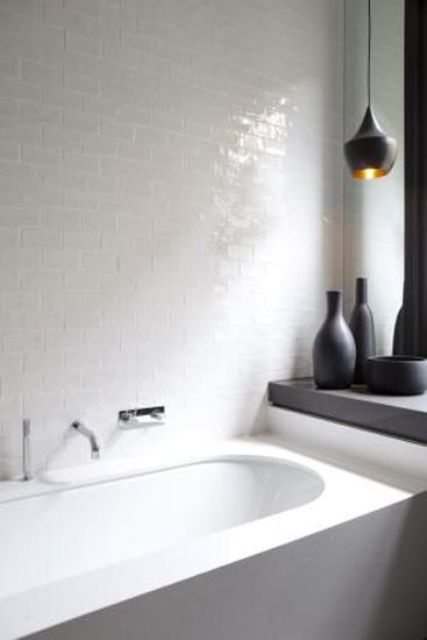 a minimalist bathroom was added a textural touch with glossy white tiles and a matte black pendant lamp