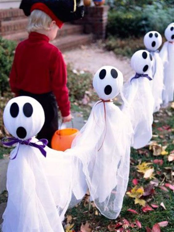 a row of cheesecloth ghosts with eyes and mouths made of black fabric