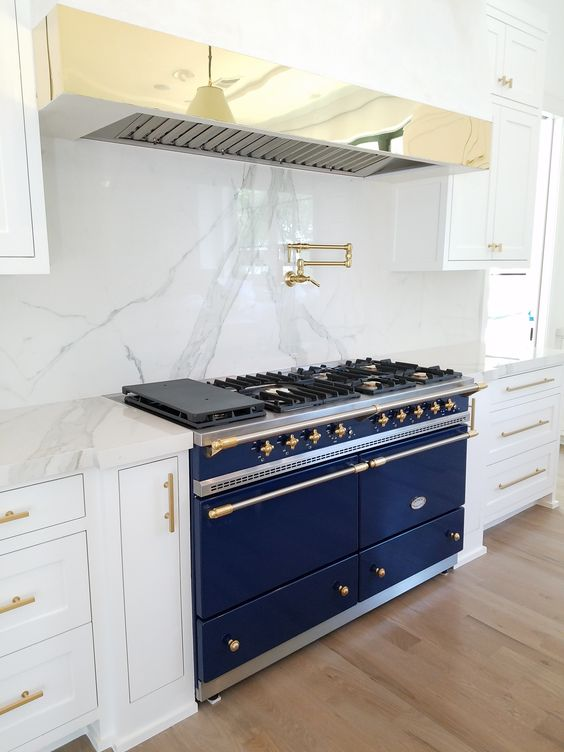 a white kitchen is spruced up with marble, a brass hood and a large cobalt blue cooker