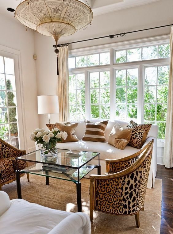 cheetah print upholstered chairs and pillows add eye-catchiness to a neutral living room