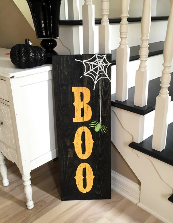 a black pallet sign with BOO letters, a web and a spider is easy to make