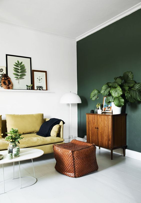 a dark green statement wall and a yellow sofa look organic and chic together