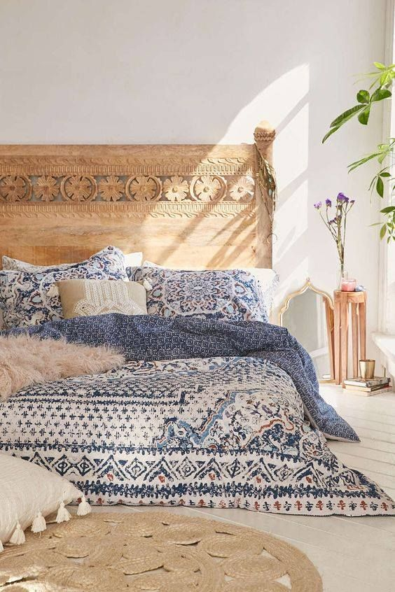 a carved wood bed with blue printed bedding is perfect for a Mediterranean feel in your bedroom