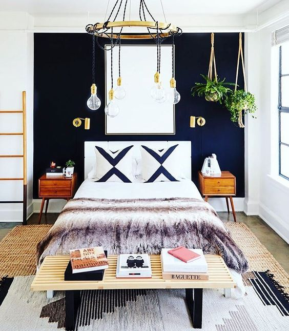 a chic boho inspired bedroom with a navy statement wall and brass touches