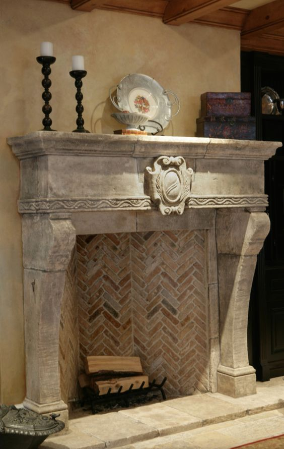 a stone fireplace with bricks inside and a metal stand with firewood