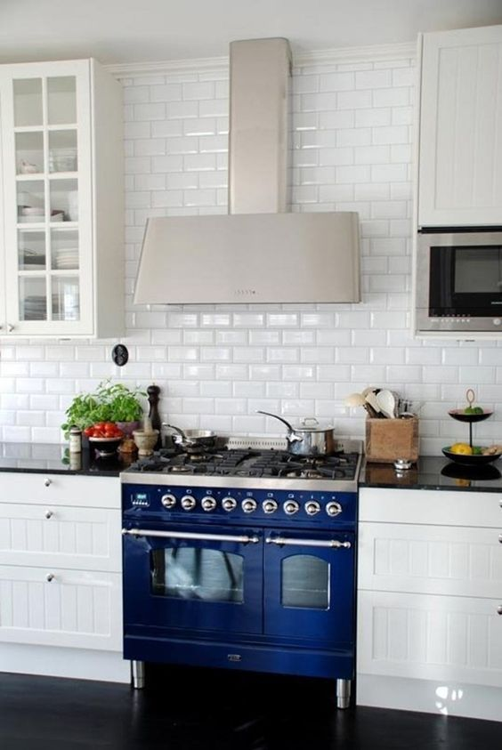 a traditional white kitchen is made eye-catchy with a subway tile backsplash and a cobalt blue cooker