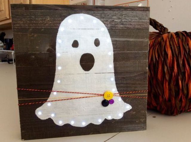 mini pallet sign with a lit up ghost, colorful yarn and buttons