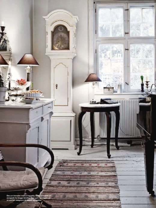 a Scandinavian kitchen with a white and gold grandfather's clock and whitewashed furniture