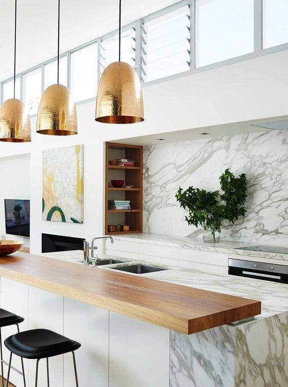 a marble kitchen island is completed with a wooden countertop and a couple of black leather stools