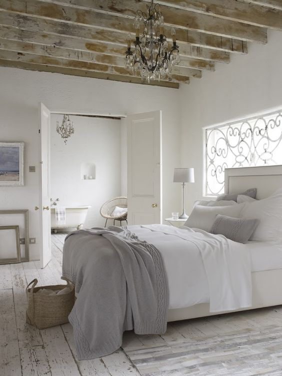 a modern white upholstered bed, rustic and shabby wooden beams and floors
