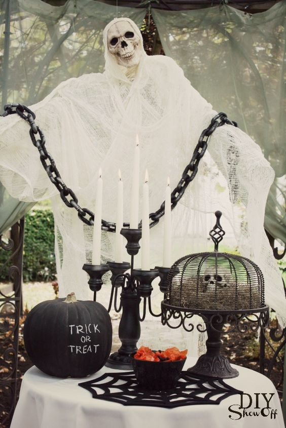 a stunning Halloween display of a cheesecloth ghost with a skull, a black pumpkin and a skull display