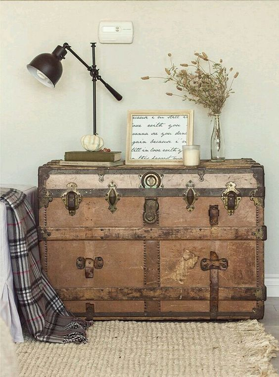 a wooden trunk with brass detailing is used as a console table for a living room