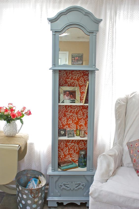 a grandfather's clock repurposed into a shelf, a mirror attached and coral print wallpaper inside