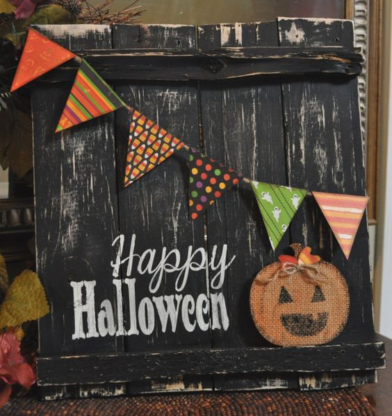 a black shabby rustic sign with a colorful banner, a burlap pumpkin applique and Happy Halloween words