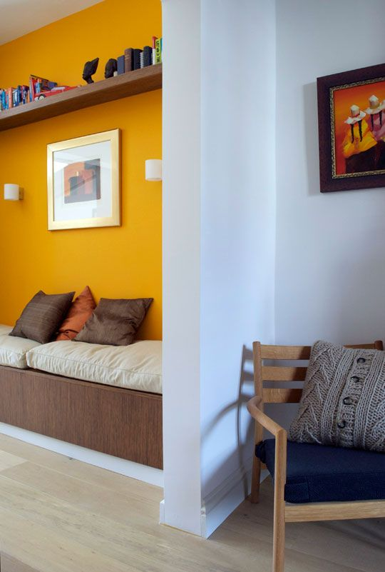 a statement wall in bold yellow helps to divide the living room and the entryway visually