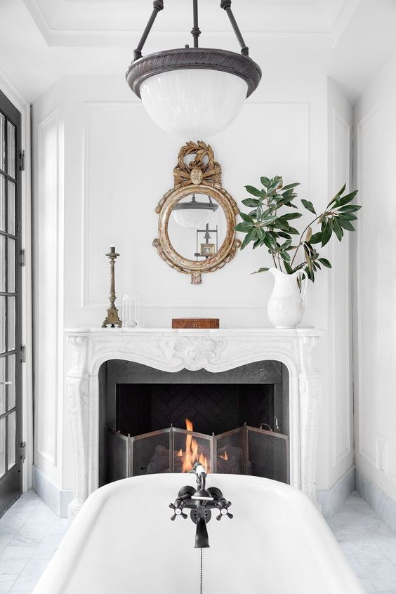 a vintage fireplace in the bathroom is working, there's a metal screen and burning firewood