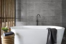 21 matte grey large scale tiles and natural wood make up a chic home spa
