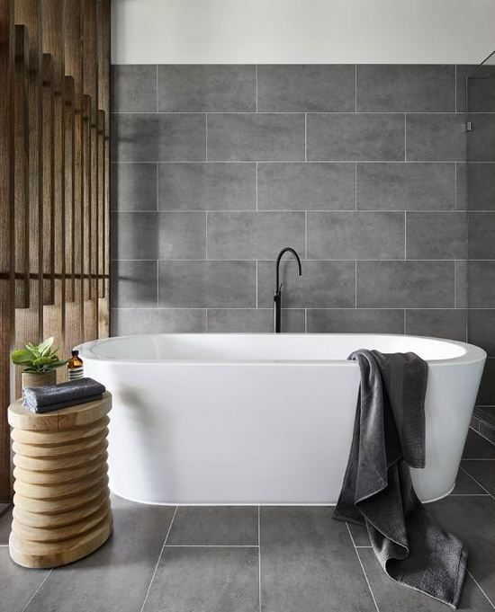 matte grey large scale tiles and natural wood make up a chic home spa