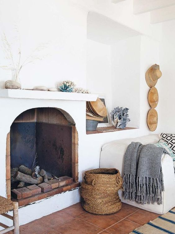the mantel is decorated with corals, shells, pebbles and straw hats on the wall add to the decor