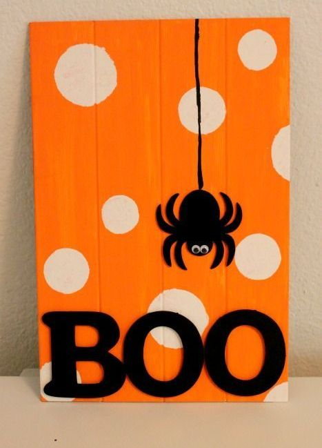 a bold orange and white polka dot sign with a spider applique and BOO letters