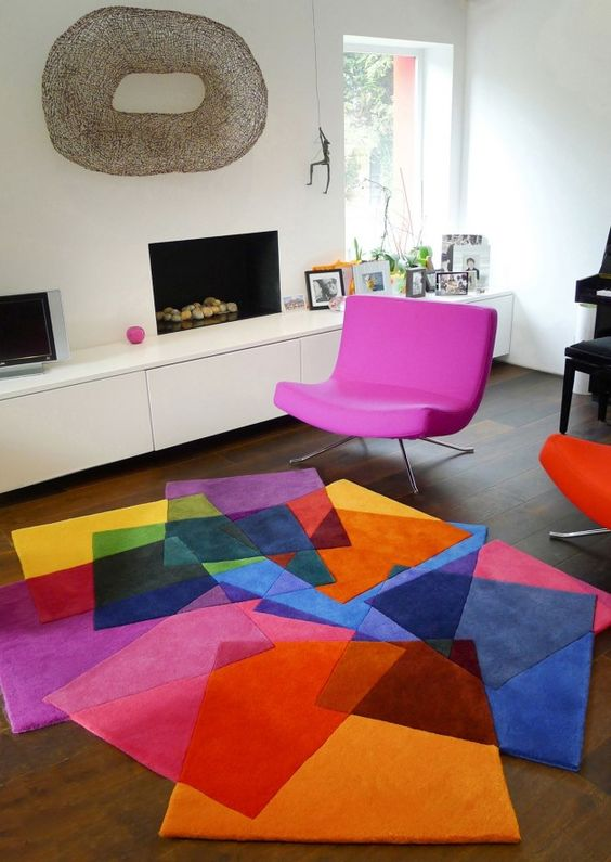 a colorful geo rug and a hot pink chair for a modern cheerful living room