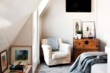 22 a small attic bedroom with a hanging TV and a bookshelf in the niche