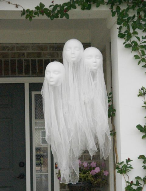 floating head hanging ghosts over the porch are made of tulle and doll heads