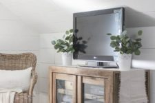23 a farmhouse glass sideboard with blankets and a TV on it