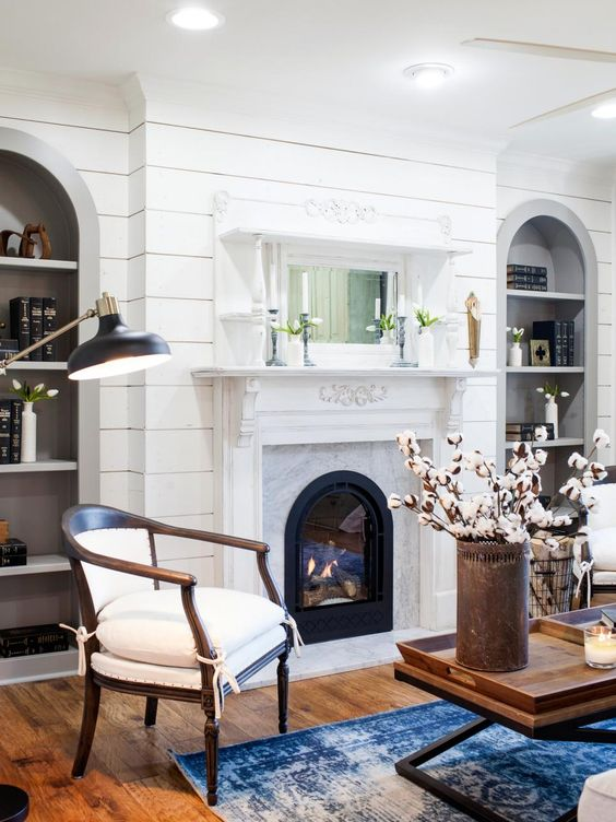 a vintage fireplace in white is used as a cover for a modern electric fireplace to add a cozy touch