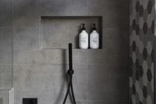 23 matte grey tiles in the shower and hex shaped ones in grey shades for an accent wall