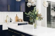 23 very dark blue kitchen cabinets with white countertops and white herringbone tiles