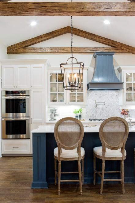 a dark blue kitchen island stands out in the white kitchen cabinets