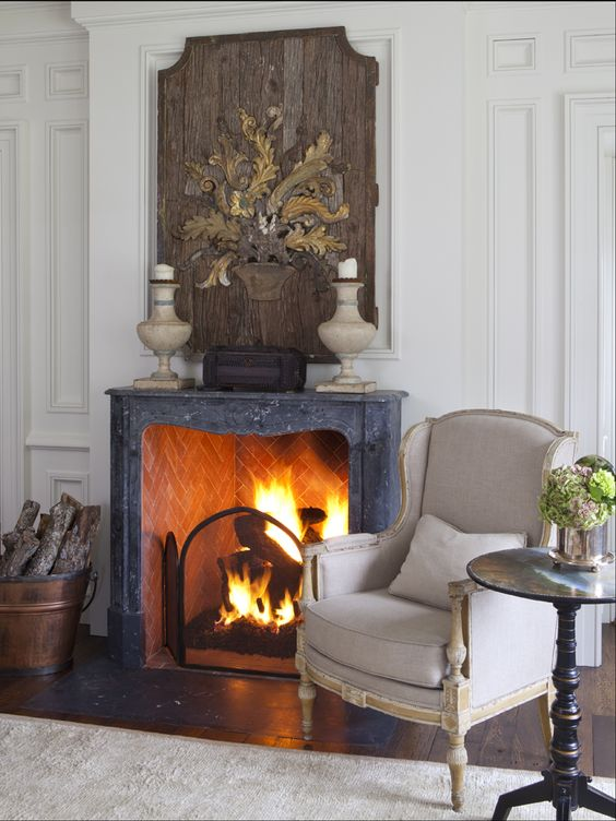 a vintage fireplace is used to make the living room cozier and is styled with a large wooden artwork
