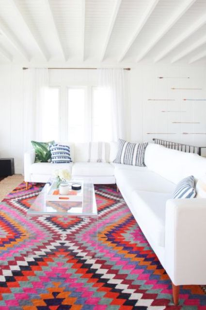 a white living room with a colorful patterned ethnical-inspired rug