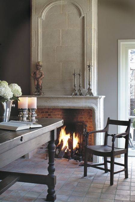 a vintage stone clad fireplace with brick inside adds a cozy feel to the dining space