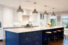 25 a white kitchen is spurced up with a large bold blue island, which is topped in white to connect to the space