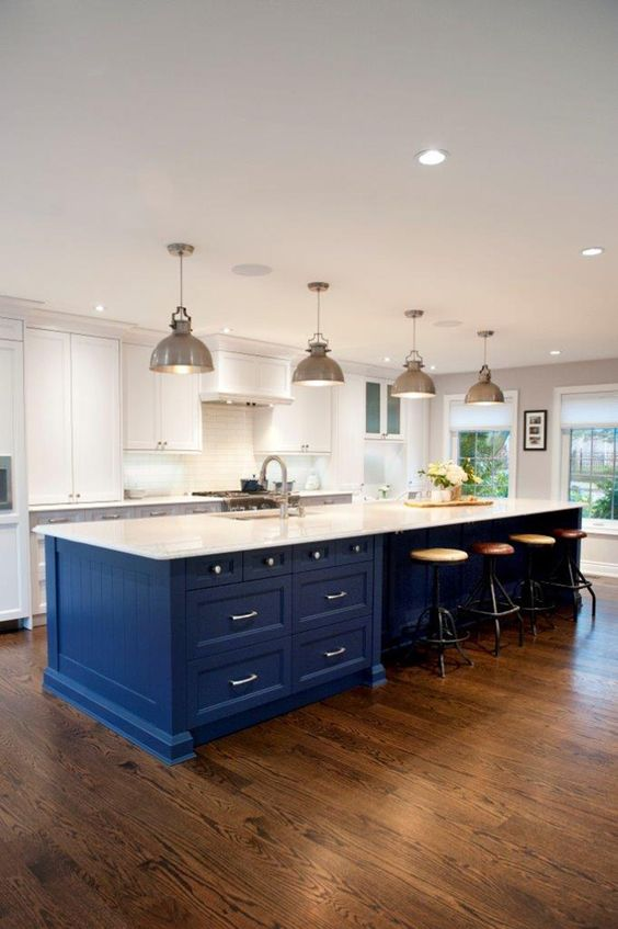 a white kitchen is spurced up with a large bold blue island, which is topped in white to connect to the space