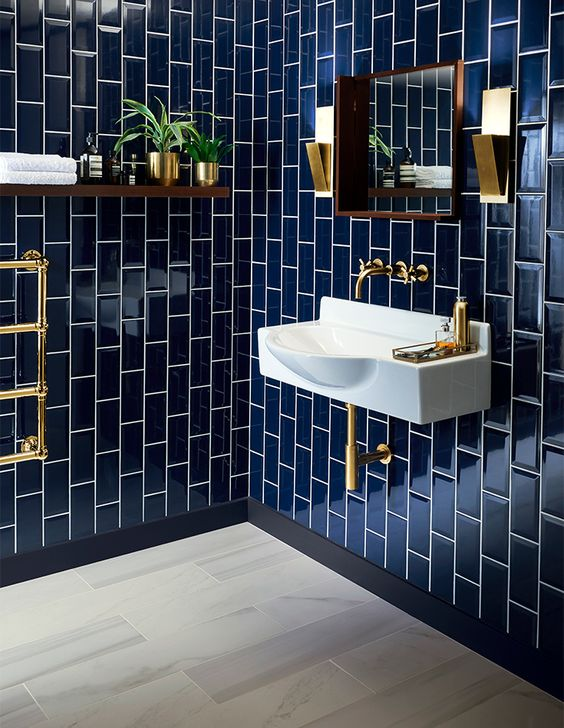 glossy navy tiles clad vertically for a bold art deco bathroom, chic brass touches