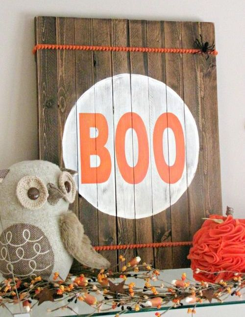 a pallet wooden sign with orange pompom trim, bold BOO letters and a couple of faux spiders