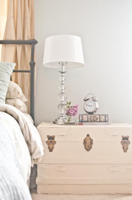a whitewashed wooden trunk as a refined bedside table for a feminine bedroom