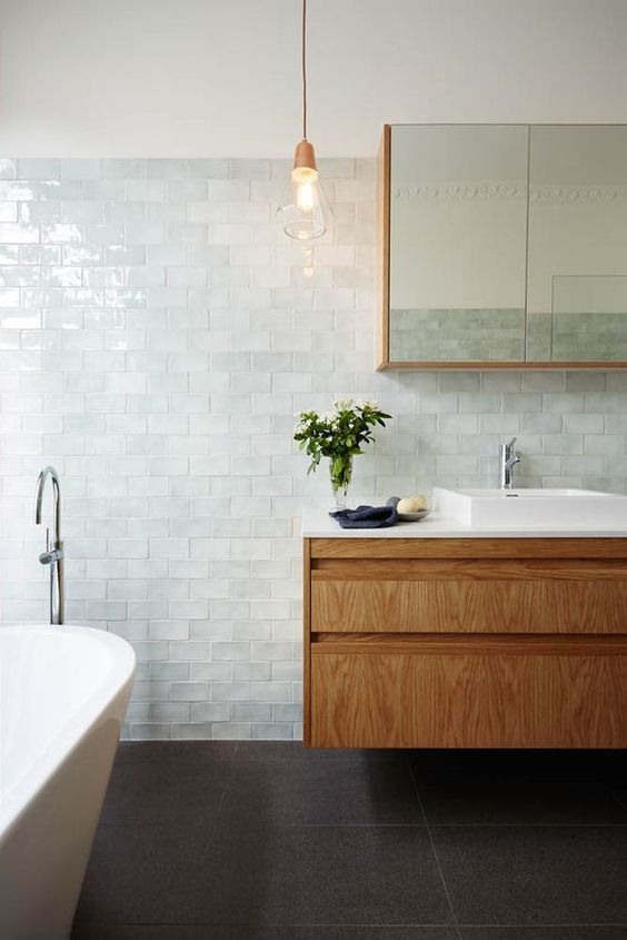 glossy tiles of a very light aqua shade look heavenly and turn the bathroom into a relaxing space